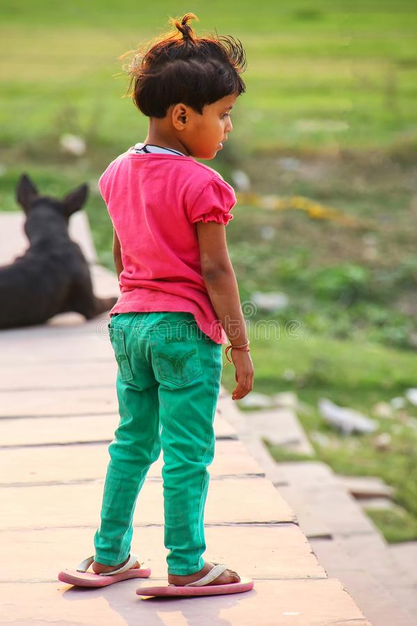 Young girl standing on the bank of Yamuna river in oversized flip-flops, Agra, Uttar Pradesh, India. Agra is one of the most populous cities in Uttar Pradesh royalty free stock photo