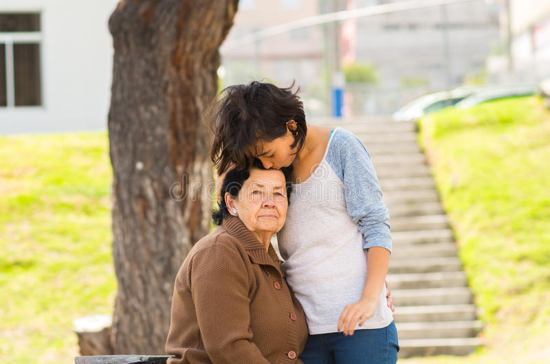 Young girl standing behind grandmother hugging and stock photos