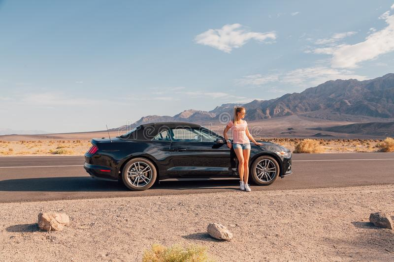 Young girl standing by the black Ford Mustang GT stock image
