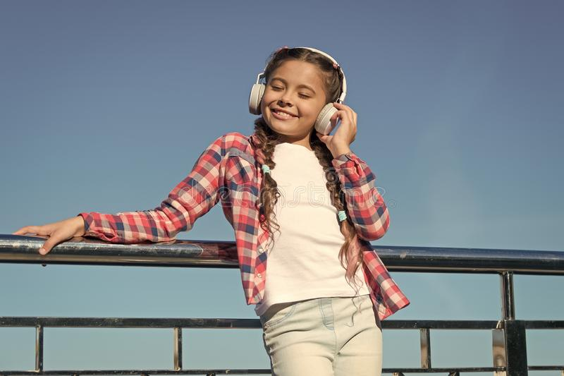 Young girl standing on bridge. Music lover. Happy childhood. Enjoying melody. Fashionable look. Music as favourite hobby. Headphones royalty free stock images