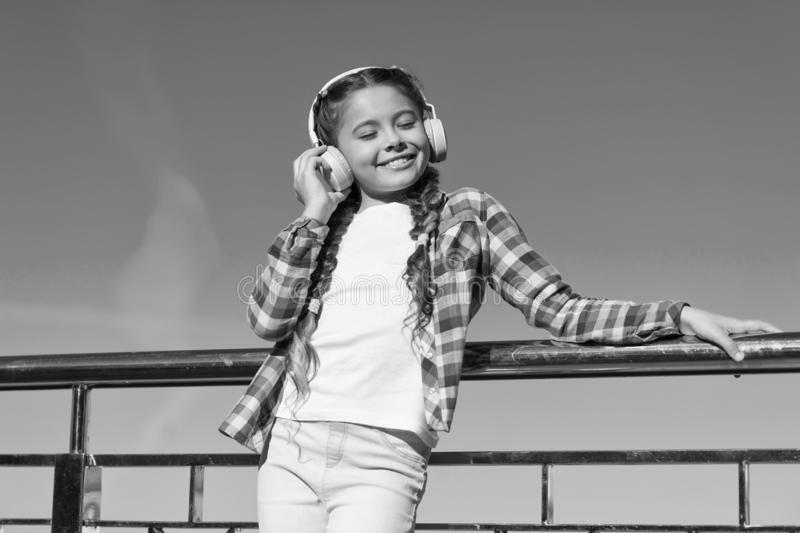 Young girl standing on bridge. Music lover. Happy childhood. Enjoying melody. Fashionable look. Music as favourite hobby. Headphones stock image
