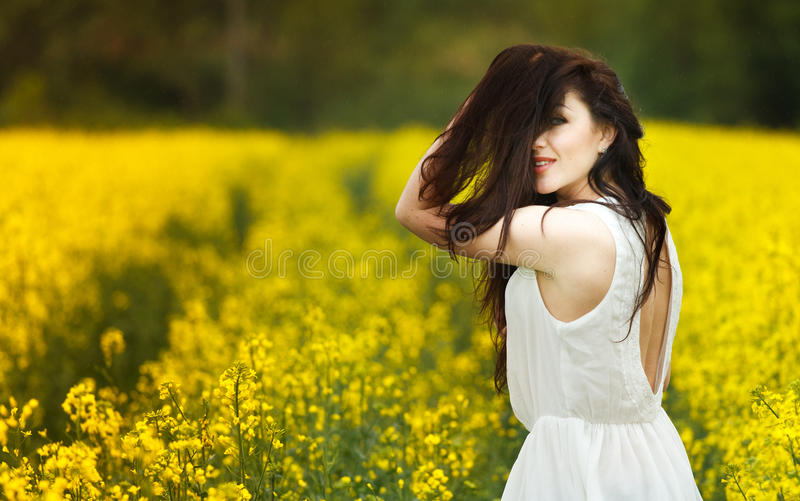 Young girl standing in a field. Close up outdoor fashion sunny portray of young beautiful girl with big amazing smile and long flu royalty free stock images