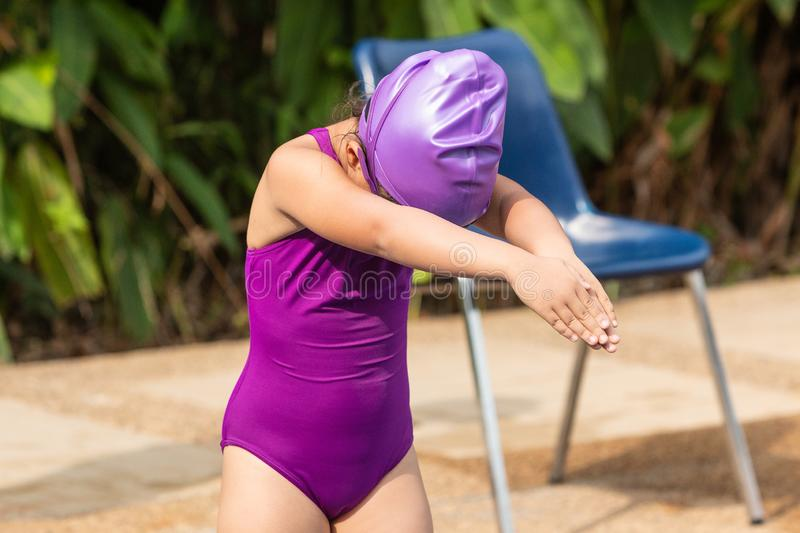 Young girl standing and getting in ready pose to start swimming royalty free stock photos