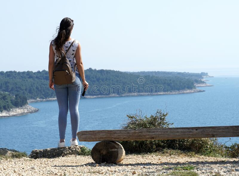 Young girl standing on a high rock and looks out over the open blue sea. Young girl standing on a high cliff and looking out over the open blue sea royalty free stock photos