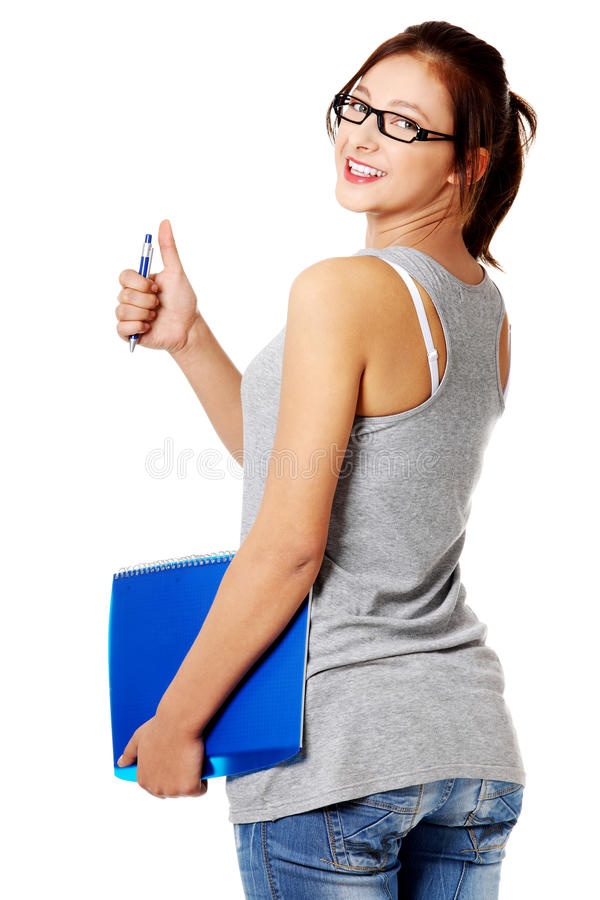 Download Young Girl Standing And Holding Notebook And Pen Stock Photo - Image: 21588188