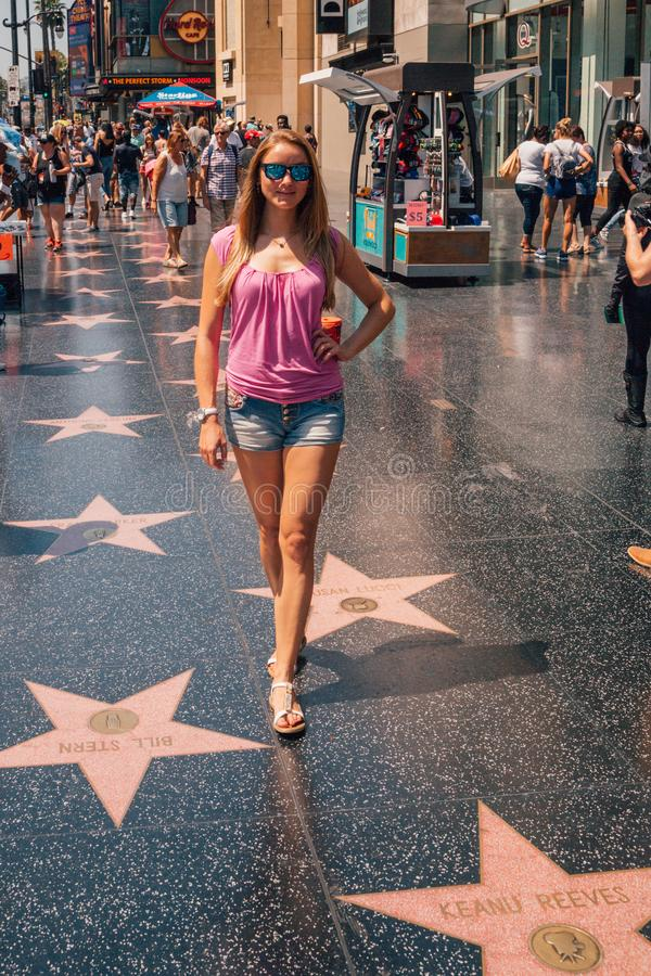 Young girl standing at the Hollywood walk of fame. Young girl walking down the walk of fame stars in Hollywood royalty free stock images