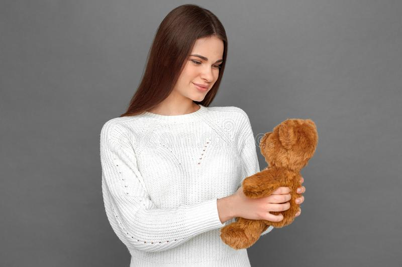 Freestyle. Young girl standing isolated on grey looking at teddy bear joyful stock photos