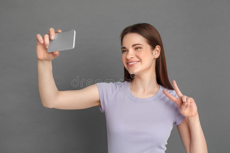 Freestyle. Young girl standing isolated on grey taking selfie on smartphone showing peace sign cheerful close-up royalty free stock photo