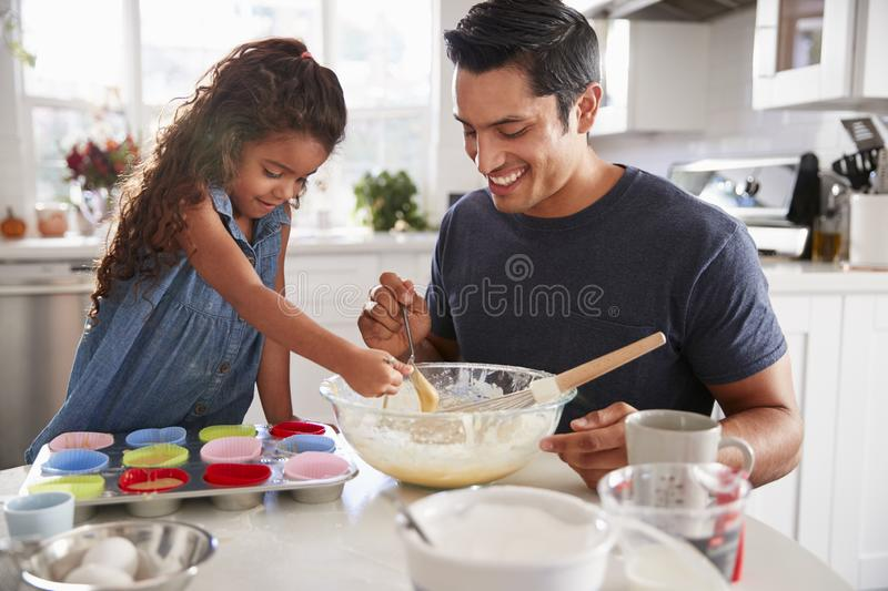 Young girl standing at the kitchen table preparing a cake mix with her father, close up stock images