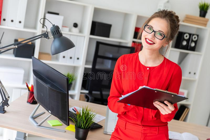 A young girl is standing leaning on a table and is holding a pencil and documents. Beautiful young girl in glasses and a red shirt is working in the office royalty free stock photos