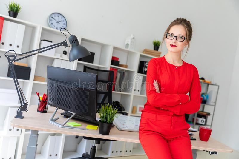 A young girl is standing leaning on a table in the office. Beautiful young girl in glasses and a red shirt is working in the office. photo with depth of field royalty free stock photography