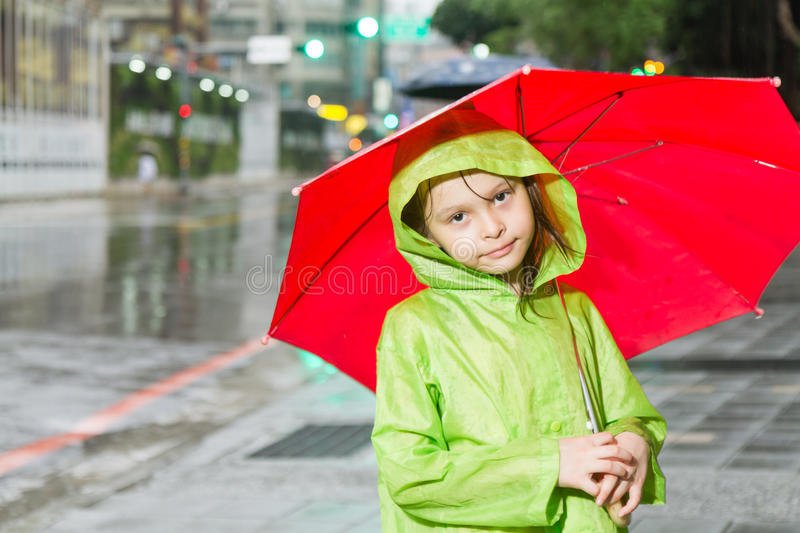 Young girl standing in rain with raincoat and umbr stock photos