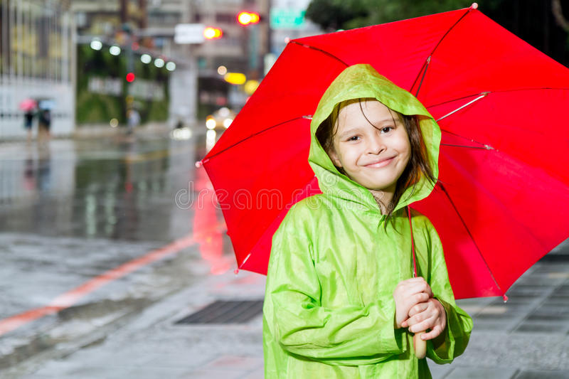 Young girl standing in rain with raincoat and umbrella royalty free stock photography