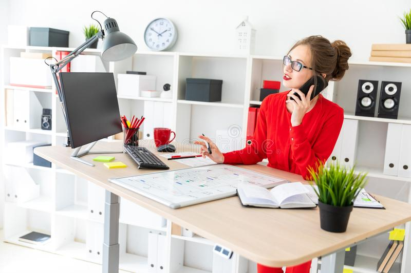 A young girl is standing at a table in the office, holding a black marker in her hand and talking on the phone. The girl. Beautiful young girl in glasses and a royalty free stock image