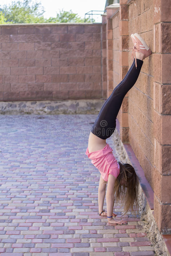 Young girl is standing upside down. stock images