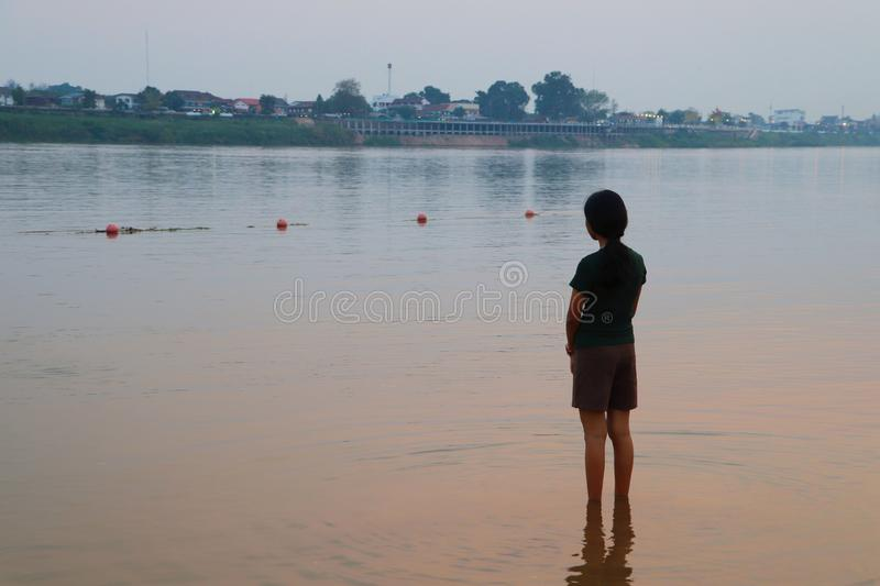 Young girl is standing in water observing the growth of the city located on the other side of the river in the quiet afternoon stock images