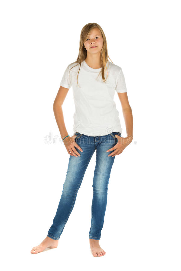 Young girl standing with white t-shirt and blue jeans over white. Young girl standing barefoot with white t-shirt and blue jeans over white background royalty free stock photo