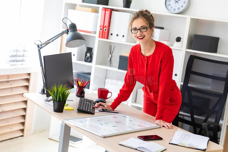 A young girl stands near the desk in the office and works with a computer, a marker and a magnetic board. Beautiful young girl in glasses and a red shirt is stock images