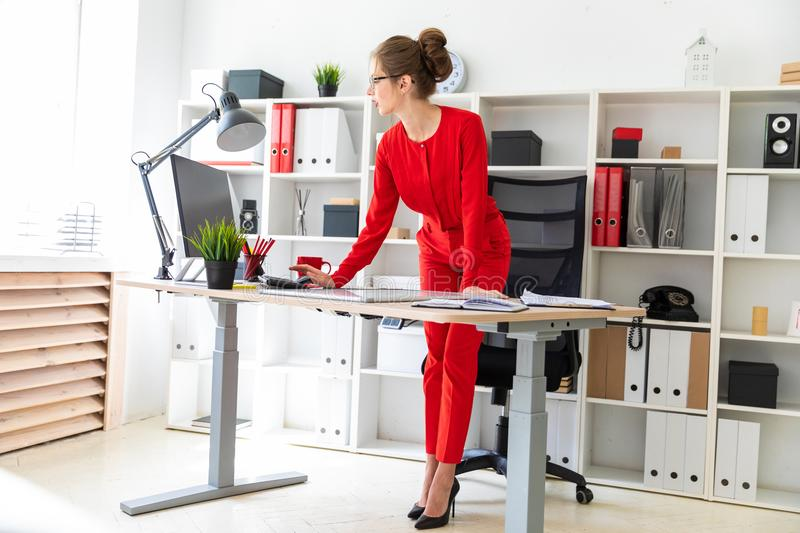 A young girl stands near the desk in the office and works with a computer, a marker and a magnetic board. Beautiful young girl in glasses and a red shirt is royalty free stock images