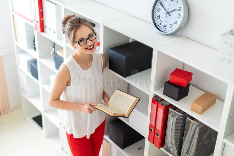 A young girl stands near the shelf and holds an open book in her hands. Beautiful young girl in glasses and a white blouse is working in the office. photo with royalty free stock images