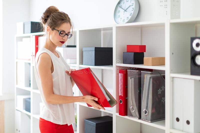 A young girl stands near the shelf and holds a red folder in her hands. Beautiful young girl in glasses and a white blouse is working in the office. photo with royalty free stock photos