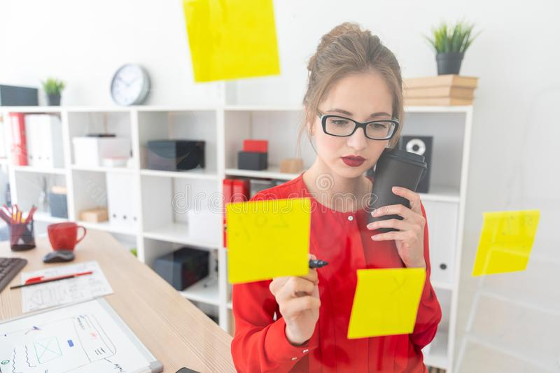 A young girl stands near a transparent board with stickers and holds a glass with coffee and a marker. Beautiful young girl in glasses and a red shirt is stock photos