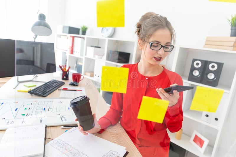 A young girl stands near a transparent board with stickers and holds a glass with coffee and telephone. Beautiful young girl in glasses and a red shirt is stock images
