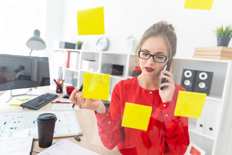 A young girl stands near a transparent board with stickers and holds a marker and a phone. Beautiful young girl in glasses and a red shirt is working in the stock photos