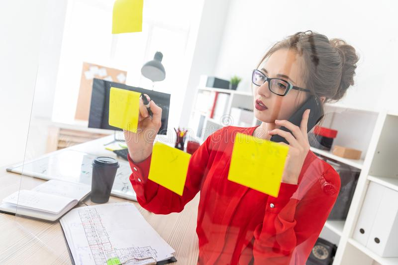 A young girl stands near a transparent board with stickers and holds a marker and a phone. Beautiful young girl in glasses and a red shirt is working in the royalty free stock photo