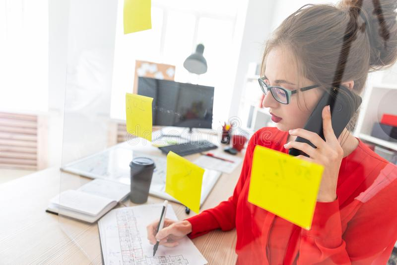 A young girl stands near a transparent board with stickers and holds a marker and a phone. Beautiful young girl in glasses and a red shirt is working in the stock images