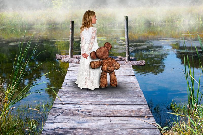 Girl, Friends, Love, Imagination, Nature. A young girl stands on a pier with her best friend for life or BFF. Her teddy bear gives a loving hug in this fantasy royalty free stock image