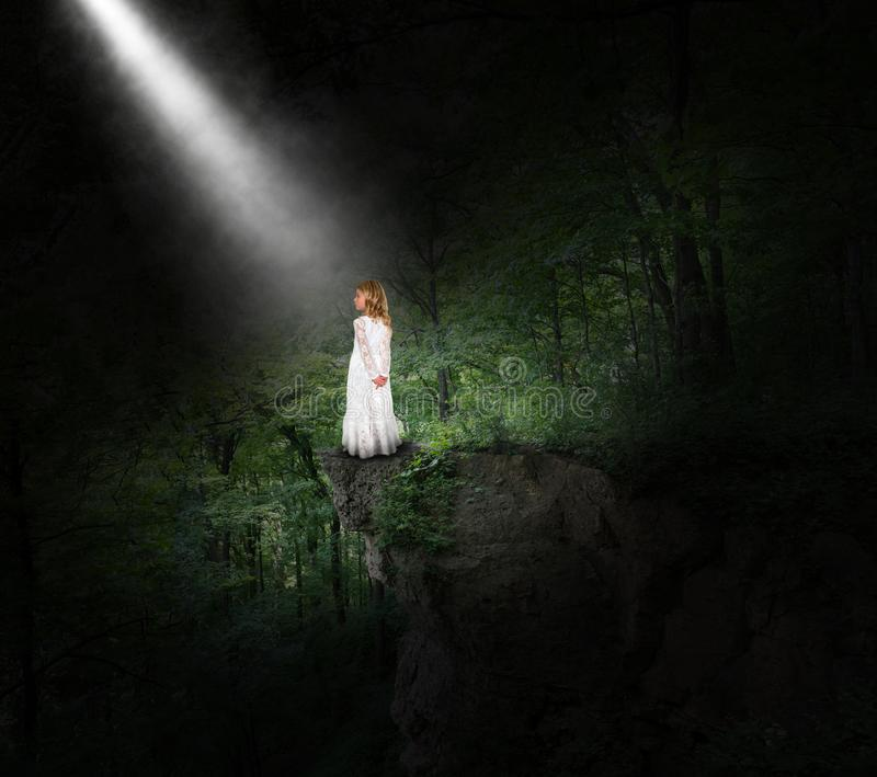 Girl, Peace, Hope, Nature, Forest. A young girl stands on a rick ledge in a deep dark woods or forest. Abstract concept for peace, hope, nature, love, and stock photos