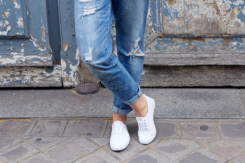 Young girl stands in the sneakers crosslegged. Close-up shoes. Trendy white sneakers and worn jeans boyfriend stock photo