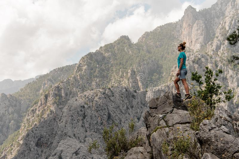 Young girl stands at top of the mountain royalty free stock image