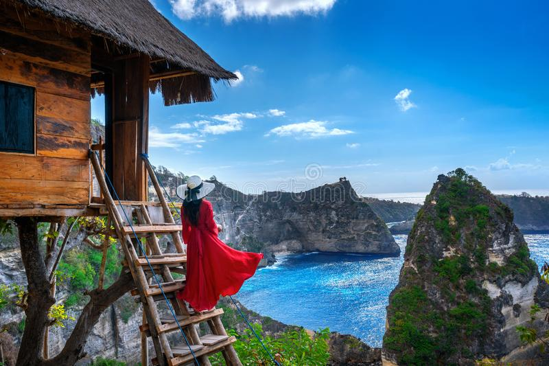 Young girl on steps of house on tree at Atuh beach in Nusa Penida island, Bali in Indonesia. stock photography