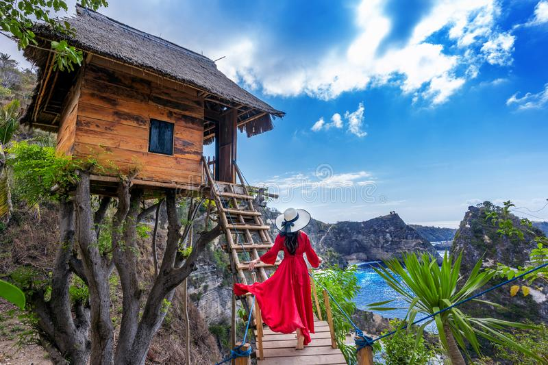 Young girl on steps of house on tree at Atuh beach in Nusa Penida island, Bali in Indonesia. royalty free stock images
