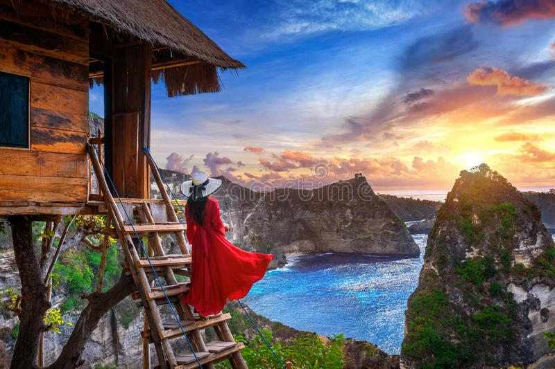 Young girl on steps of house on tree at sunrise in Nusa Penida island, Bali in Indonesia stock images