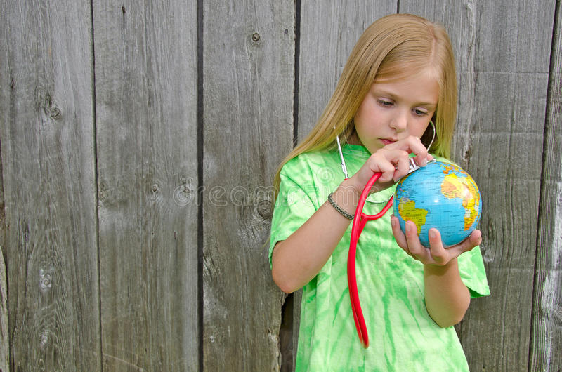 Young girl with stethoscope on world globe royalty free stock photos