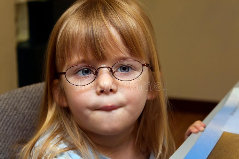 Young Girl With Strabismus or Ocular Palsy Trying On A Pair Of N. A young girl with ocular palsy or strabismus tries on a pair of metal frame, new glasses. She stock images