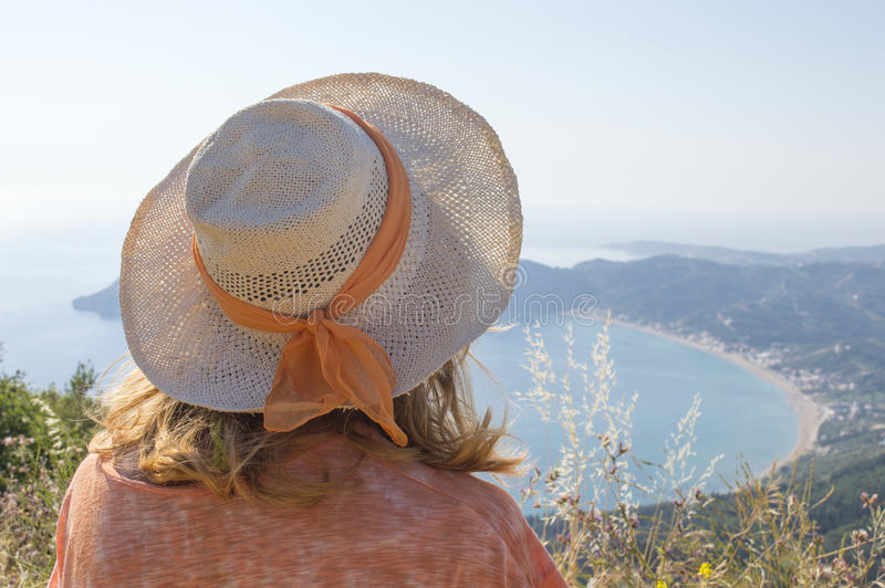 Young girl with straw hat looking at the seaside from extraordinary viewpoint stock photos