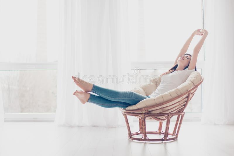 Young girl is stretching in modern armchair in light livingroom. She is sleepy and dreamy, wearing casual clothes royalty free stock photography