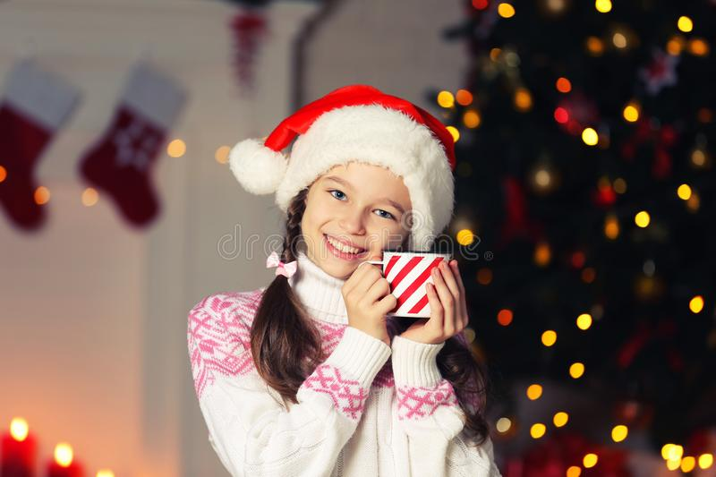 Young girl with striped mug. Near christmas tree at home royalty free stock photo