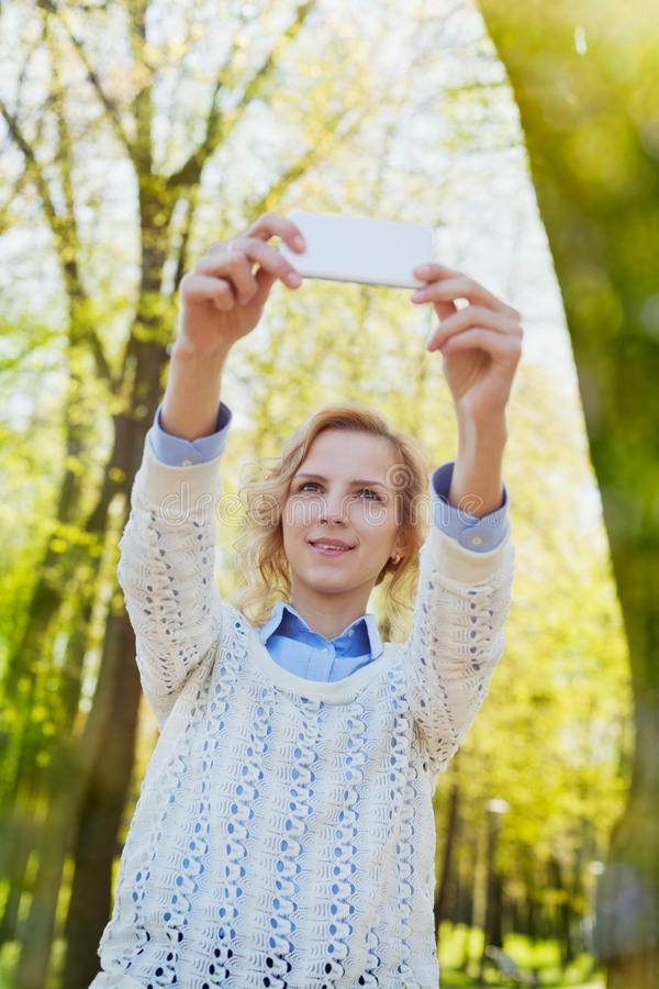 Young girl student having fun and taking selfie photo on smartphone camera outdoor in green summer park in sunny day, teenage tran royalty free stock photos