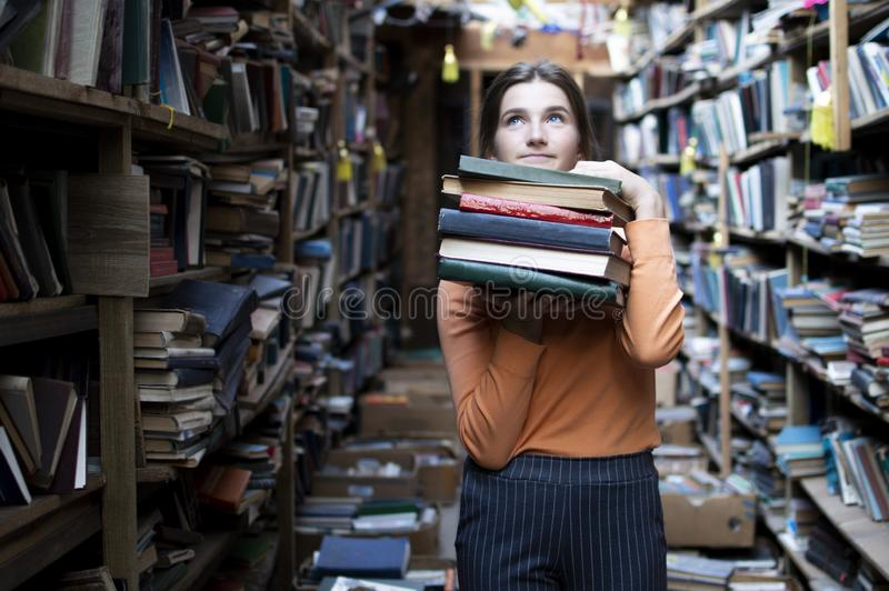 Girl student holds a stack of books in the library, she searches for literature and offers to read, a woman prepares for study, royalty free stock photo