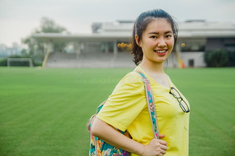 Young girl student portrait smiling on grass field in the afternoon in campus stock photo