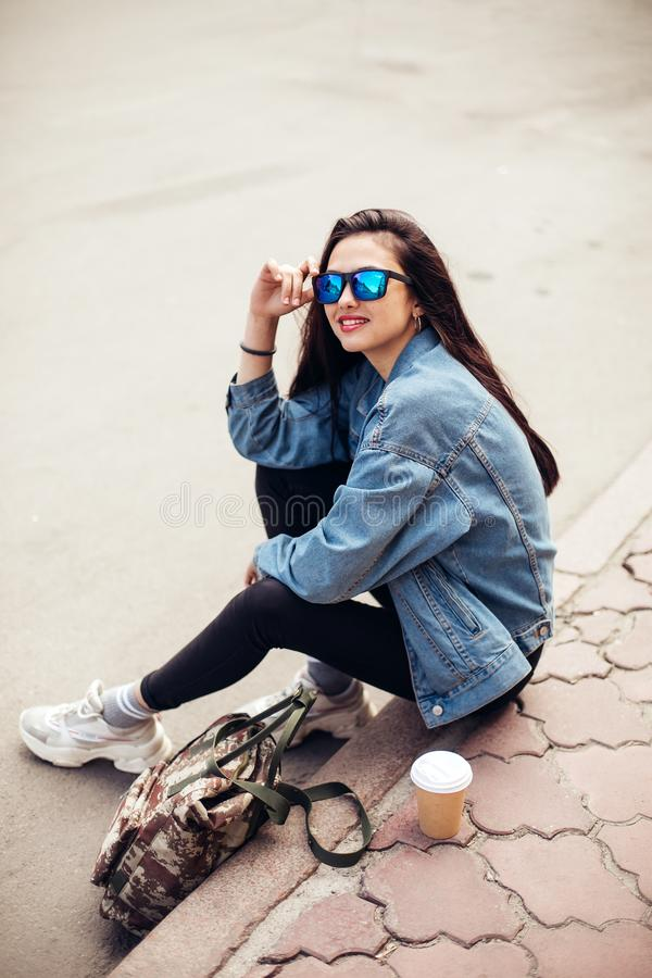Young girl student is sitting on the pavement. Wear jeans and drink coffee. Young beautiful model girl in sunglasses smiles stock photography
