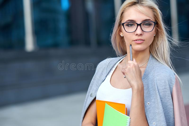 Young girl student smiling and holding a folder stock photos