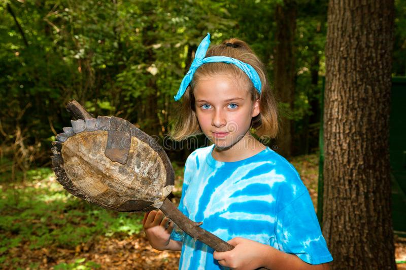 Young Girl In Blue Tie Dye and Bandana Holds the Rotting Shell o stock photos