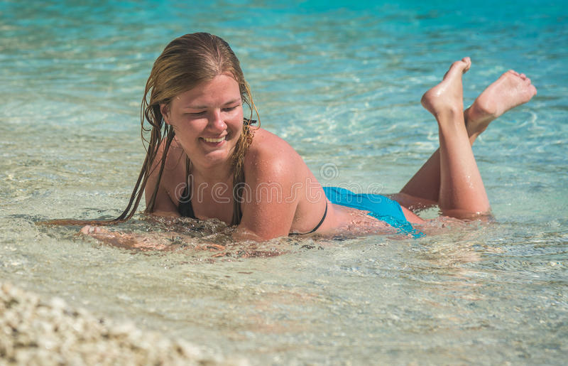 Young girl sunbathing in sea water splashing around her. On one of Lefkada beaches in Greece stock photography