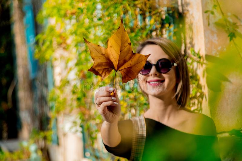 Young girl in sunglasses holding a leaf royalty free stock photos